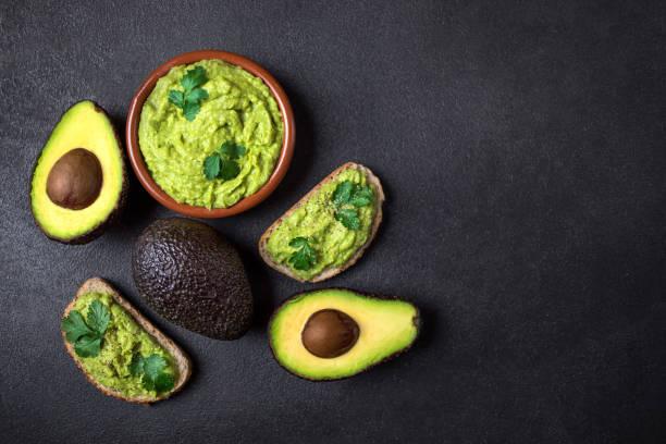 """mexicano dip molho guacamole com abacate em uma tigela de barro em fundo preto. abacate se espalhou. vista superior. copyspace """"n - guacamole - fotografias e filmes do acervo"""