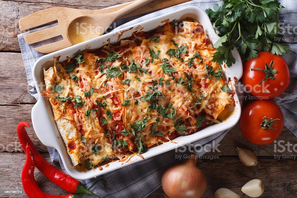Mexican enchilada in a baking dish horizontal top view close-up stock photo