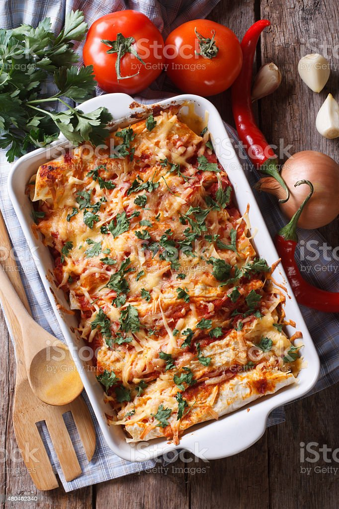 Mexican enchilada in a baking dish vertical top view close-up stock photo