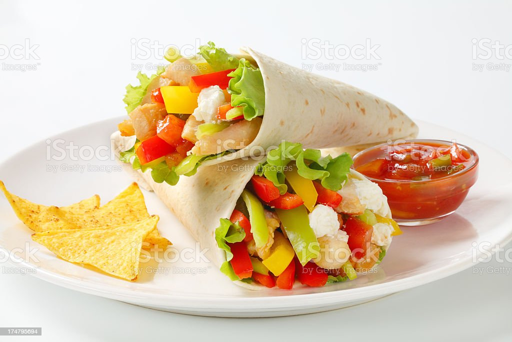 mexican fajitas (tortilla wraps) on a white plate stock photo