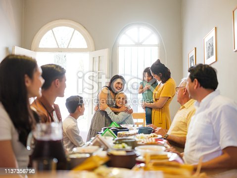 A mexican family eating lunch at the table and taking turns to stand up and embracing grandmother.