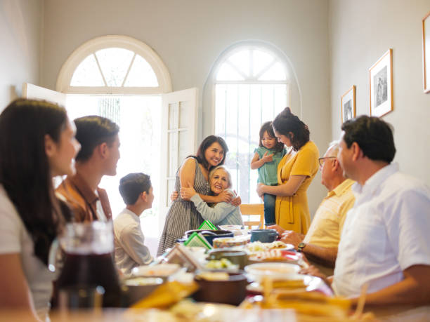 Mexican family at lunch table embracing grandmother A mexican family eating lunch at the table and taking turns to stand up and embracing grandmother. mexican culture stock pictures, royalty-free photos & images