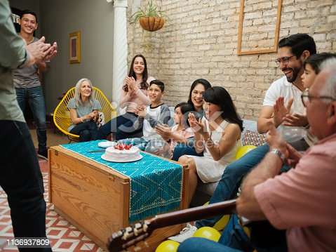 A mexican family sitting together, clapping for a birthday and smiling at each other.
