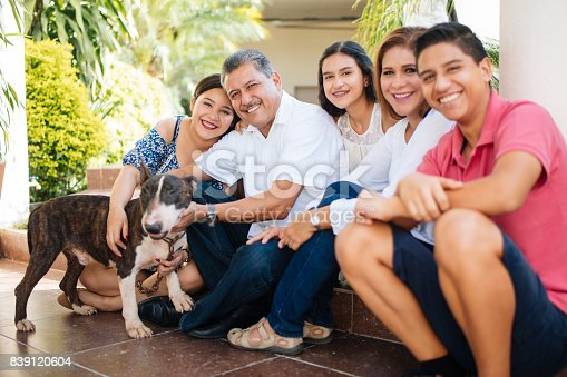 istock Mexican family with dog sitting on floor and smiling 839120604