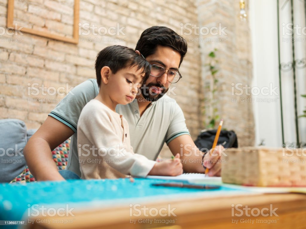 Mexican father and young son drawing on notebook at home - Стоковые фото 30-34 года роялти-фри