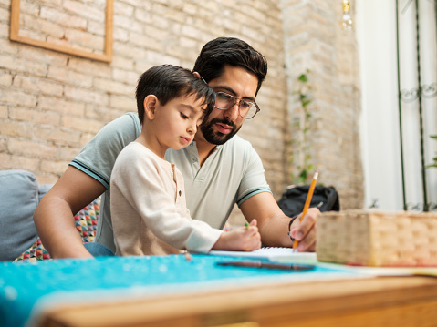 Mexican Father And Young Son Drawing On Notebook At Home — стоковые фотографии и другие картинки 30-34 года