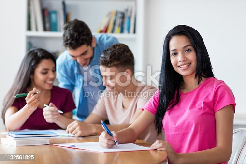 istock Mexican female student learning with group of students 1132561825