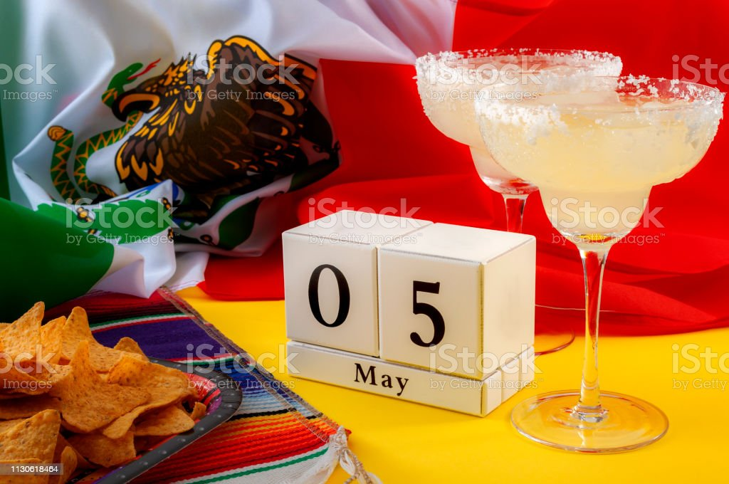 Mexican fiesta and Cinco de Mayo party concept theme with block calendar set on May 5th, traditional rug or serape, two margaritas, bowl of tortilla chips and the flag of Mexico stock photo