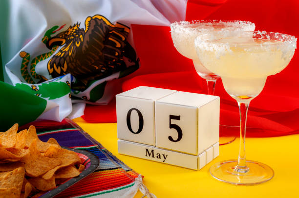 mexican fiesta and cinco de mayo party concept theme with block calendar set on may 5th, traditional rug or serape, two margaritas, bowl of tortilla chips and the flag of mexico - cinco de mayo stock photos and pictures