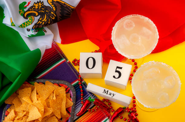 mexican fiesta and cinco de mayo party concept theme with block calendar set on may 5th, jalapeno pepper beads necklace, traditional rug or serape, two margarita glasses, chips and the mexican flag - cinco de mayo party stock photos and pictures