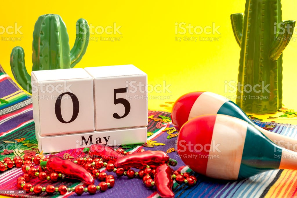 Mexican fiesta and Cinco de Mayo party concept theme with calendar on May 5th, red jalapeno pepper necklace, maracas, cactus, traditional rug and sombrero shaped confetti on yellow background stock photo