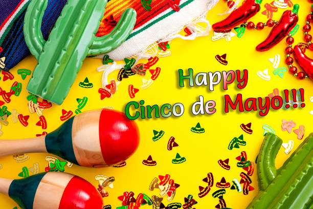 mexican fiesta and latino party concept theme with jalapeno pepper necklace, maracas, cactus and traditional rug covered in sombrero shaped confetti on yellow background with happy cinco de mayo text - cinco de mayo party stock photos and pictures