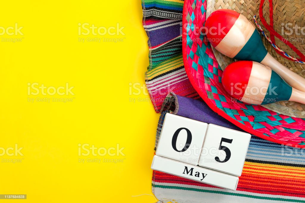 Mexican fiesta poster and Cinco de Mayo party concept theme with calendar on may 5th, red and blue maracas, sombrero and traditional rug on yellow background with copyspace stock photo
