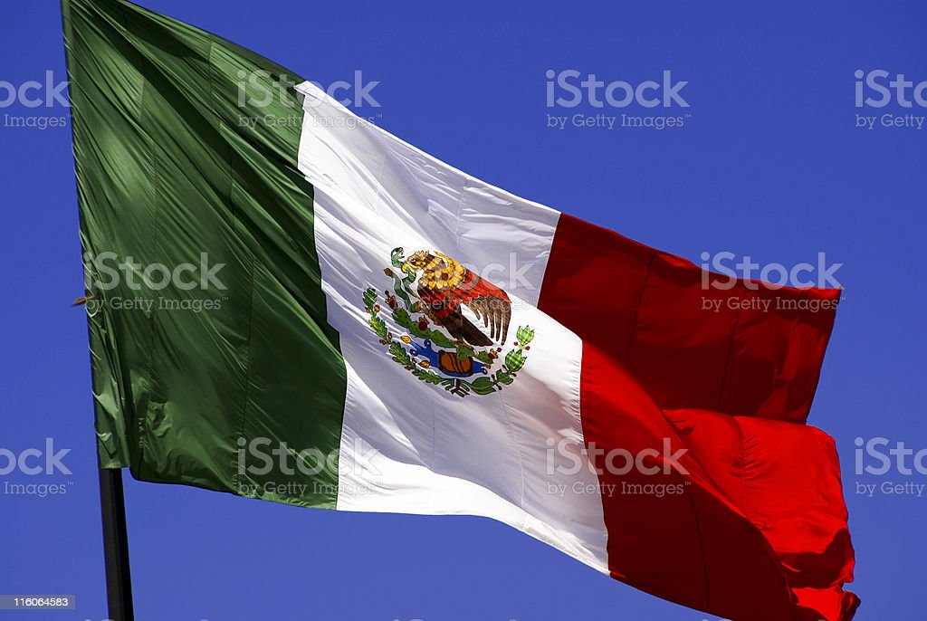 Mexican flag at full mast waving in the wind stock photo