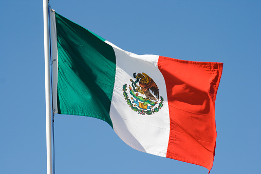 Mexican Flag, National Banner of Mexico Waving Against Blue Sky