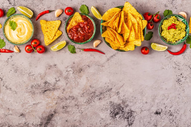 Mexican food background: guacamole, salsa, cheesy sauces with nachos Mexican food background: guacamole, salsa, cheesy sauces with nachos, top view. salsa sauce stock pictures, royalty-free photos & images