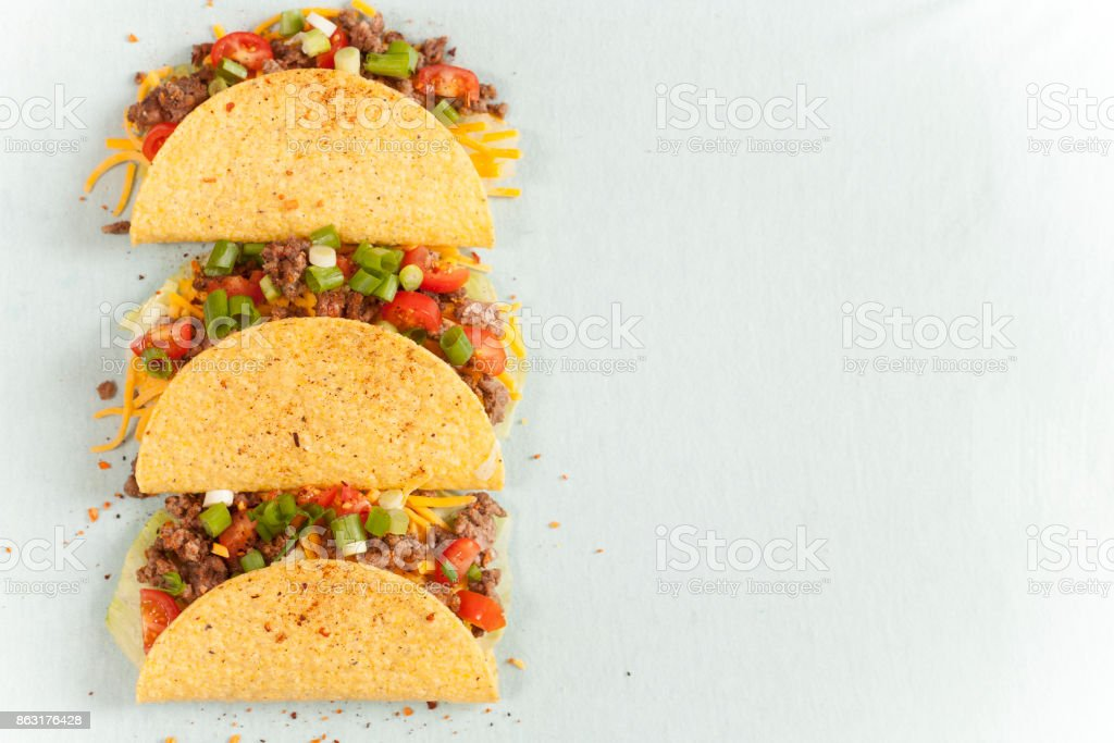 Mexican food crunchy beef tacos in a row. stock photo