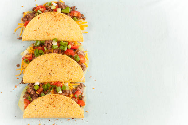 mexican food crunchy beef tacos in a row. - mexican food stock photos and pictures