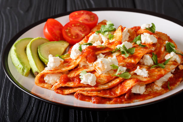 mexikanische küche: entomatadas mit bauernkäse, tomatensauce, greens und avocado nahaufnahme. horizontale - kräuterfaltenbrot stock-fotos und bilder