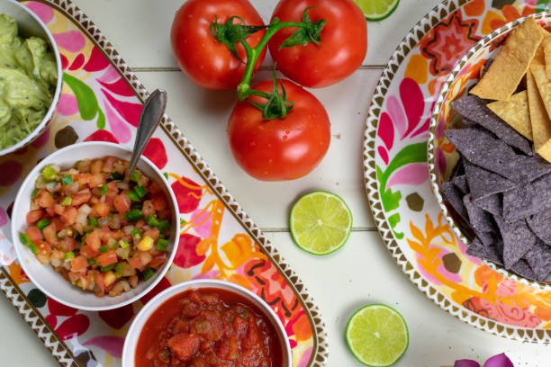 mexican food flat lay - chips, salsas and fresh ingredients - cinco de mayo party stock photos and pictures