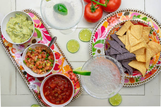 mexican food flat lay - top view of chips, salsas, fresh ingredients  and margaritas - cinco de mayo party stock photos and pictures