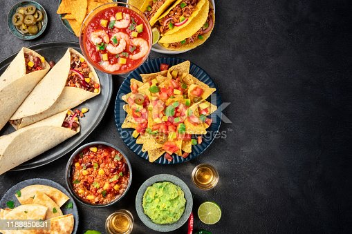 Mexican food, many dishes of the cuisine of Mexico, flat lay, top shot on a black background with a place for text. Nachos, tequila, guacamole, burritos, chili con carne and copy space
