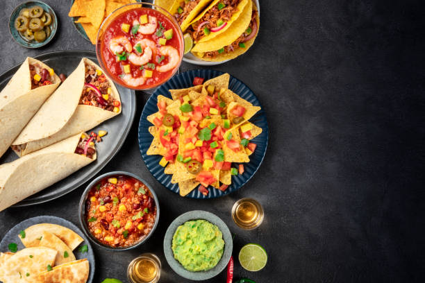 Mexican food, many dishes of the cuisine of Mexico, flat lay, top shot on a black background with a place for text. Nachos, tequila, guacamole, burritos, chili con carne and copy space stock photo