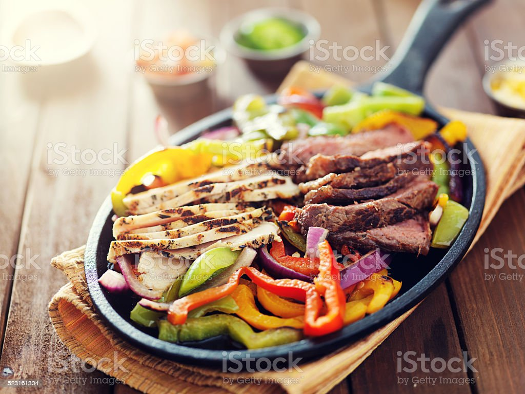 mexican food - skillet fajitas with steak and chicken stock photo