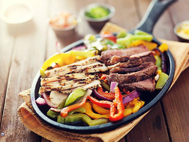 comida mexicana-sartén plana con bistec, pollo y fajitas de - comida mexicana fotografías e imágenes de stock