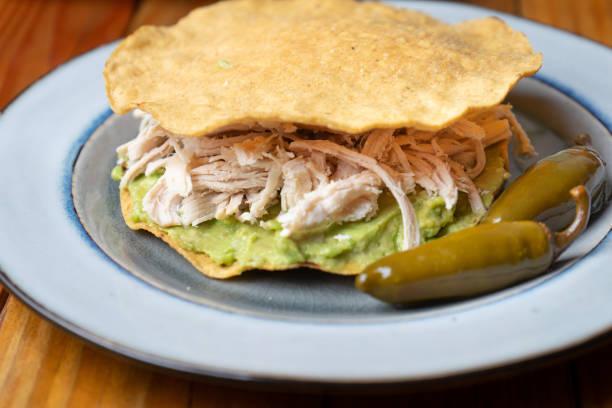 Comida mexicana. Tortilla tostada con pollo y guacamole