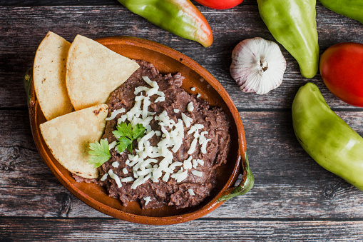 Mexican fried beans called Frijoles Refritos, plate of black beans on a wooden table in Mexico