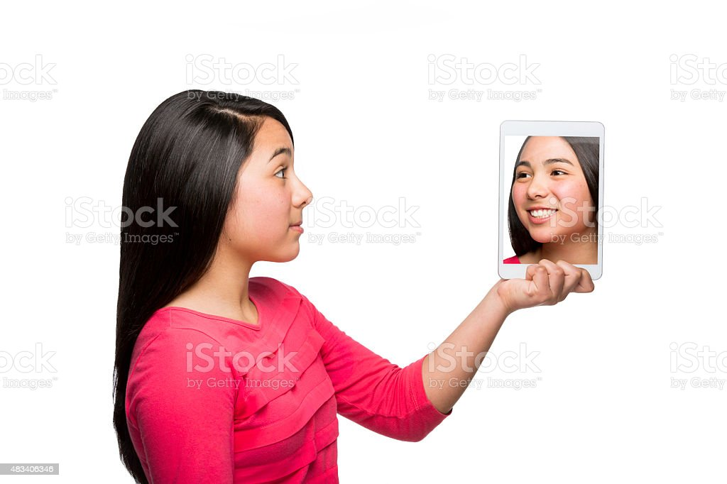 Mexican girl looking at her photo on digital tablet stock photo