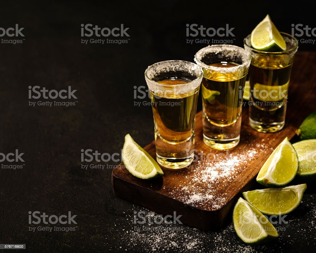 Mexican Gold Tequila with lime and salt on wooden table стоковое фото