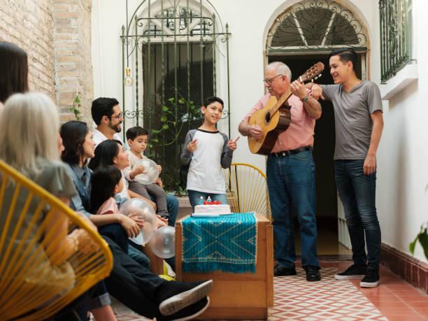 mexikanischer großvater spielt gitarre vor der familie - gitarren geburtstagstorten stock-fotos und bilder