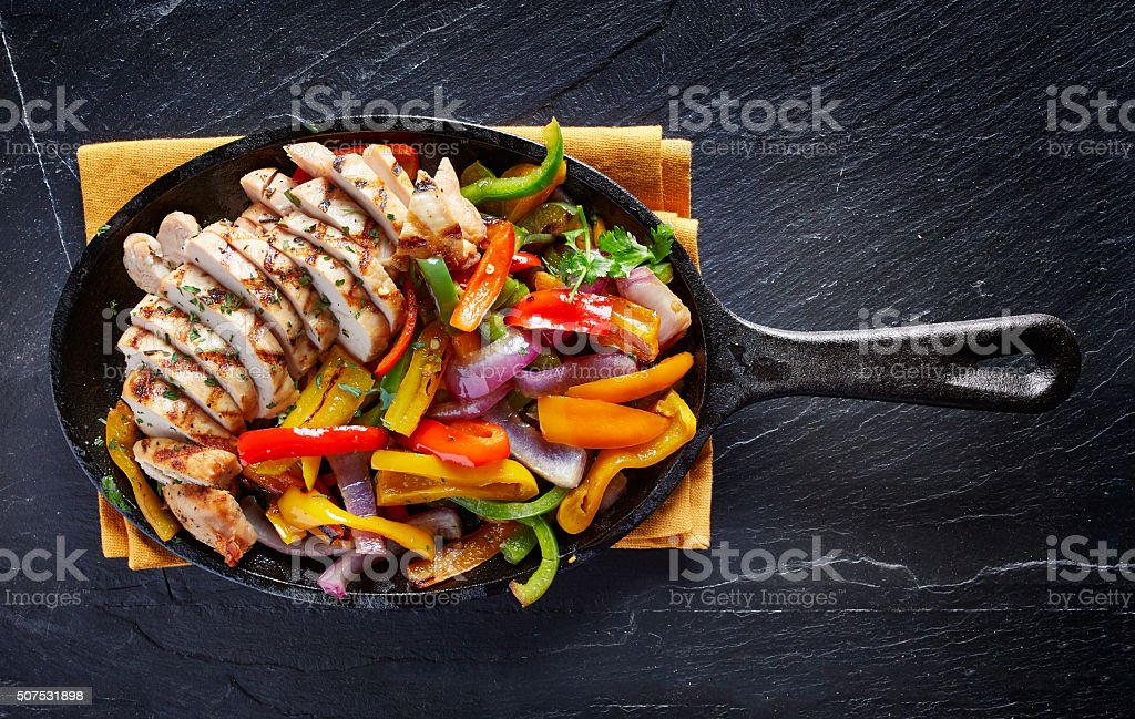 mexican grilled chicken fajitas in iron skille stock photo