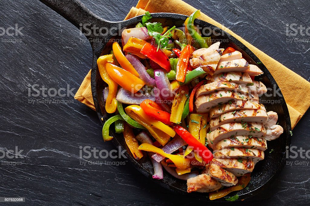 mexican grilled chicken fajitas in iron skillet stock photo