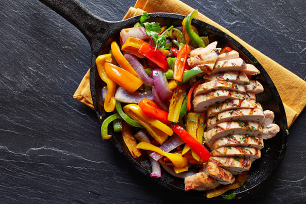 mexican grilled chicken fajitas in iron skillet - meat pan stockfoto's en -beelden