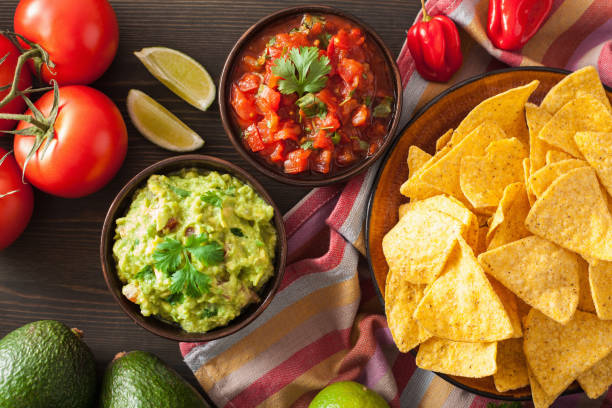 mexican guacamole and salsa dip, nachos tortilla chips mexican guacamole and salsa dip, nachos tortilla chips salsa sauce stock pictures, royalty-free photos & images