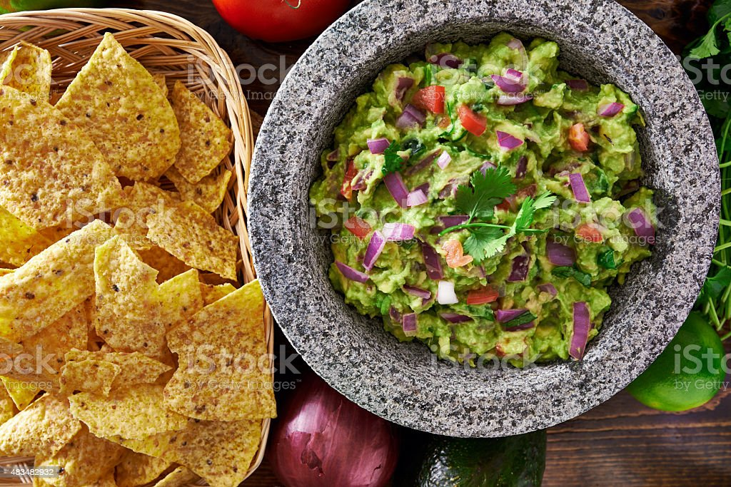 mexican guacamole in molcajete with tortilla chips stock photo
