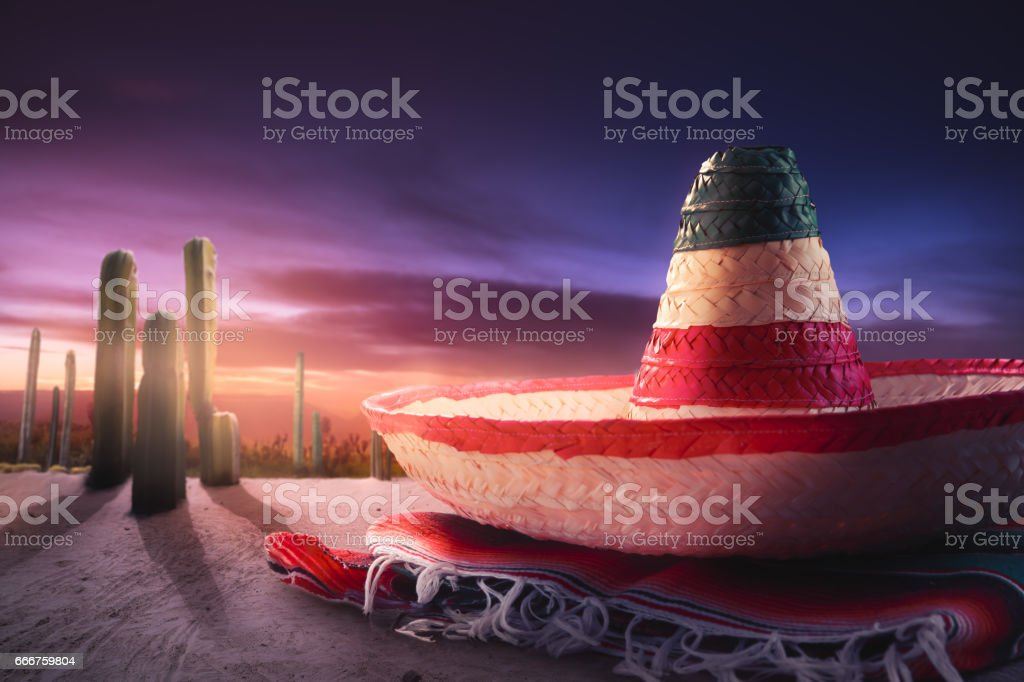 Mexican hat 'sombrero' on a 'serape' in a mexican desert at twilight foto stock royalty-free