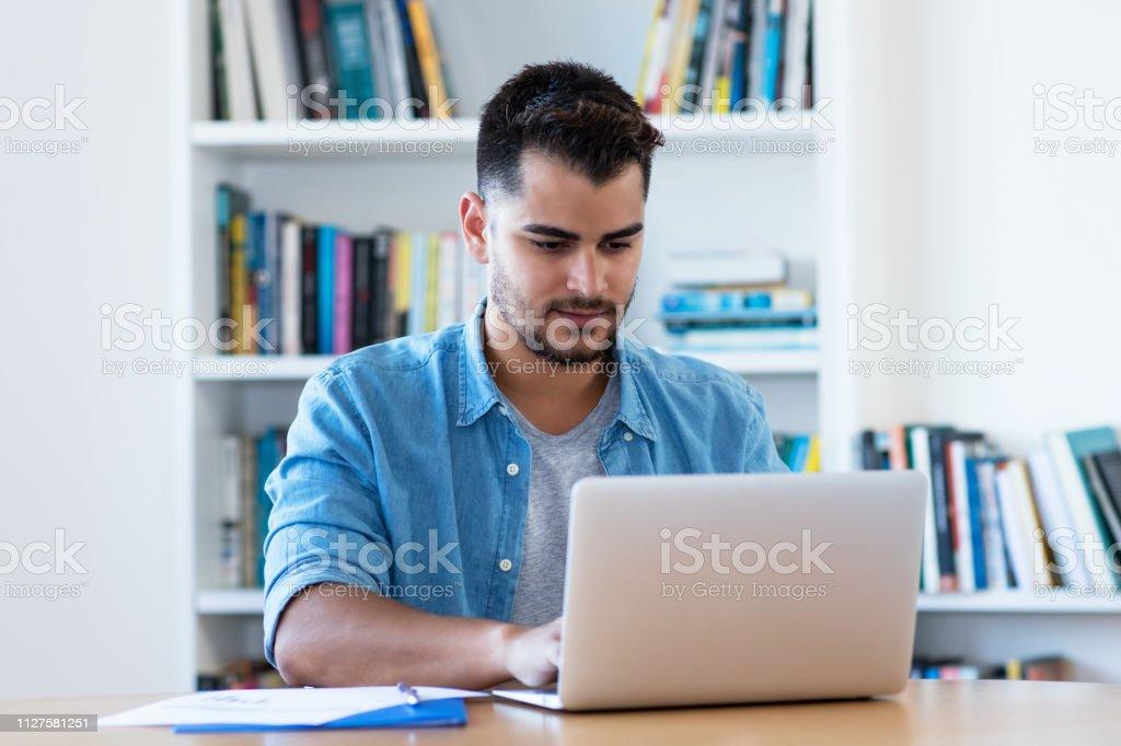 Hombre hipster mexicano en el trabajo con ordenador portátil - foto de stock