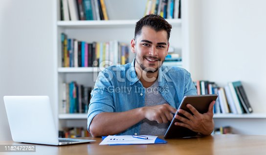 istock Mexican hipster man reading news with tablet 1182472752