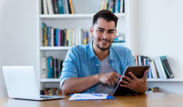 Hombre hipster mexicano leyendo noticias con tableta - foto de stock