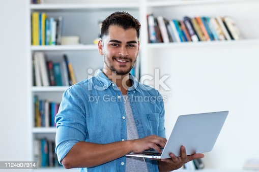 1127582480istockphoto Mexican hipster man with beard and computer 1124507914