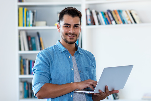 istock Mexican hipster man with beard and computer 1124507914