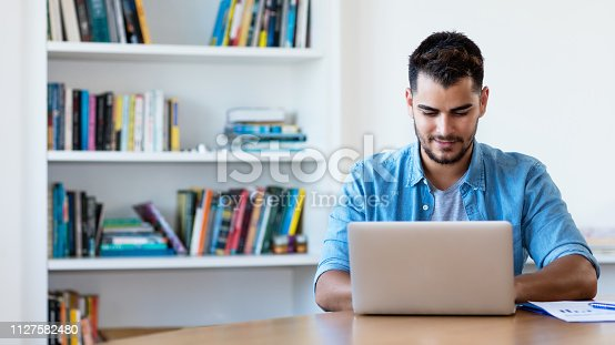 istock Mexican hipster man working with computer 1127582480