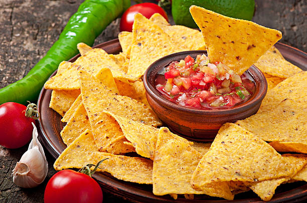 Mexican nacho chips and salsa dip in bowl Mexican nacho chips and salsa dip in bowl on wooden background salsa sauce stock pictures, royalty-free photos & images
