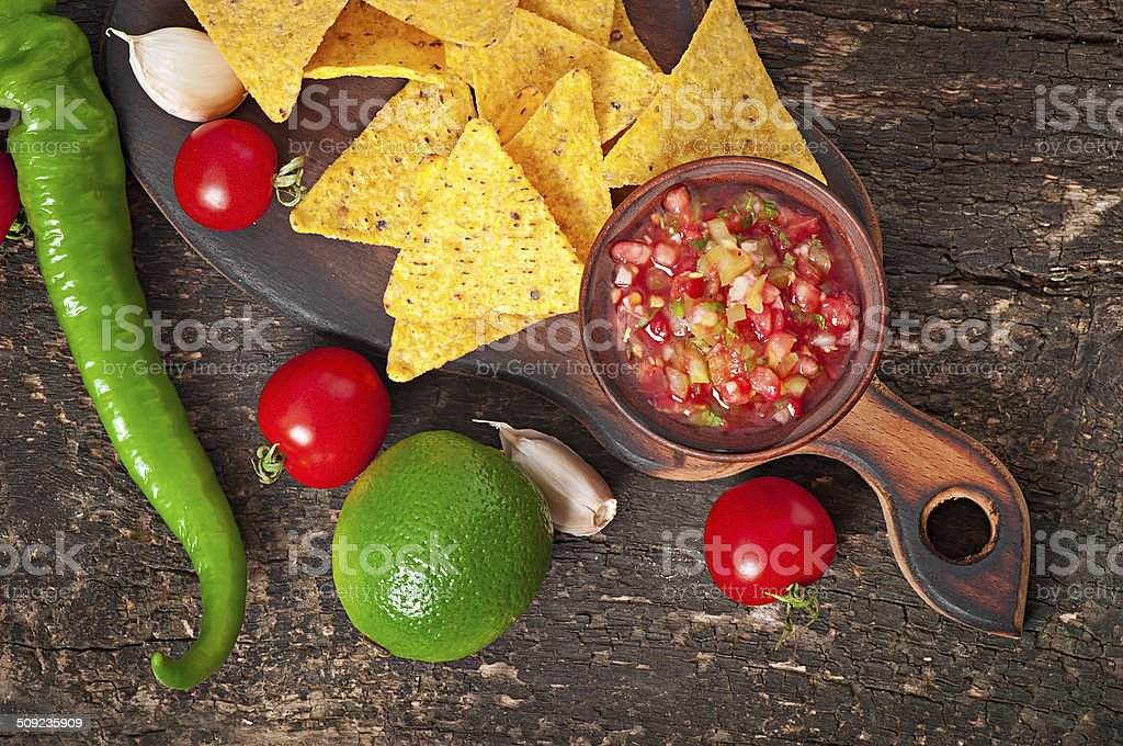 Mexican nacho chips and salsa dip in bowl stock photo