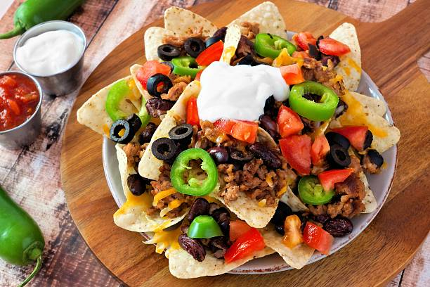 Mexican nacho chips on a wooden paddle board Mexican nacho chips topped with sour cream, ground meat, jalapenos, tomatoes, beans and melted cheese on a wooden paddle board sour cream stock pictures, royalty-free photos & images