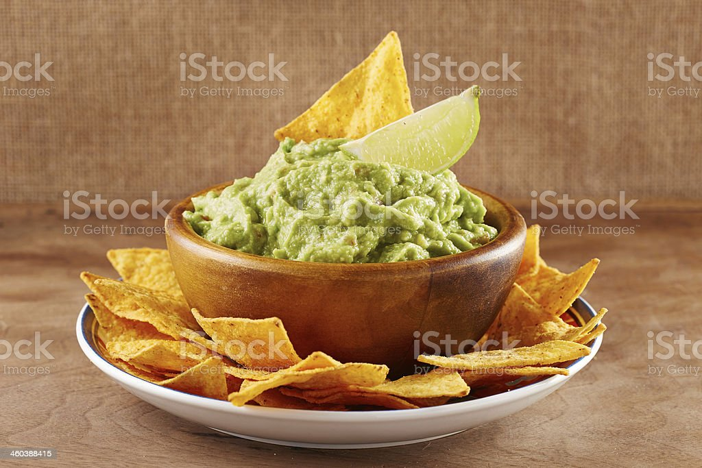 Mexican nacho chips with guacamole in a bowl and a lime stock photo